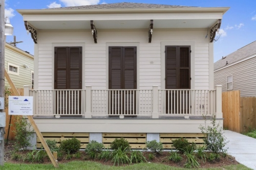 Front porch with wood shutters and backets on single family cottage in Central City