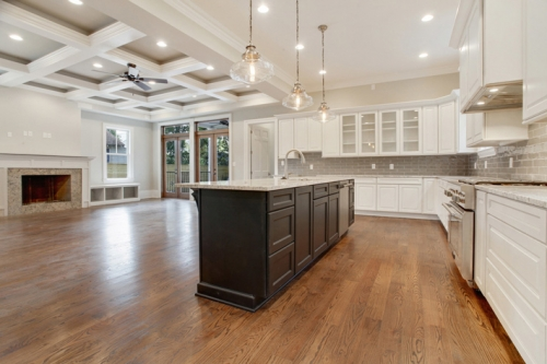 Open plan kitchen, dining, and family room with french doors opening onto back porch